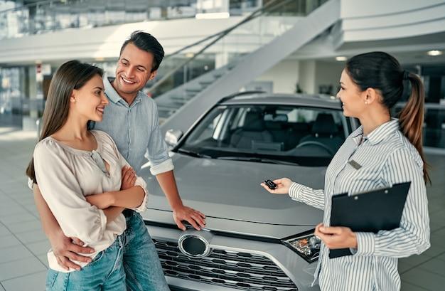 Schönes glückliches paar hat im autohaus ein auto gekauft und erhält die schlüssel vom manager.
