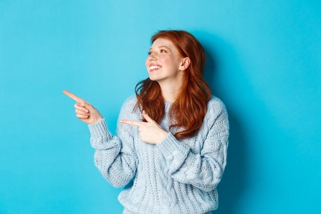 Schönes glückliches rothaariges mädchen, das mit den fingern nach links zeigt und das logo erfreut betrachtet, im pullover vor blauem hintergrund stehend.