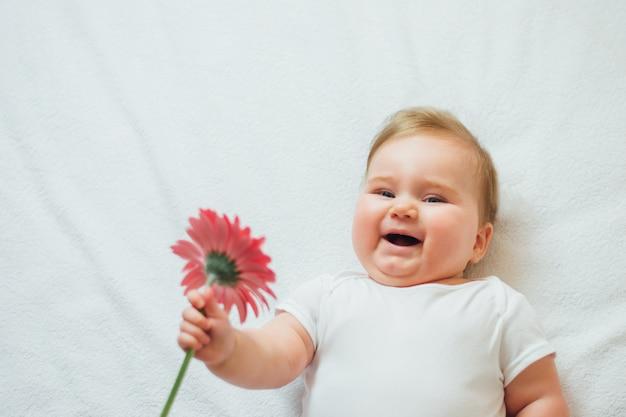 Schönes glückliches säuglingsbaby, das auf weißen blättern liegt, die eine blume halten. glückliches kind mit blume, die weißen bodysuit trägt. freiraum.