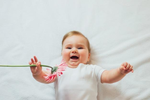 Schönes glückliches säuglingsbaby, das auf weißen blättern liegt, die eine blume halten. glückliches kind mit blume, die weißen bodysuit trägt.