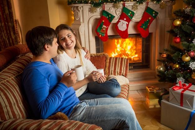 Schönes glückliches verliebtes paar, das tee auf dem sofa am brennenden kamin trinkt, der für weihnachten verziert wird
