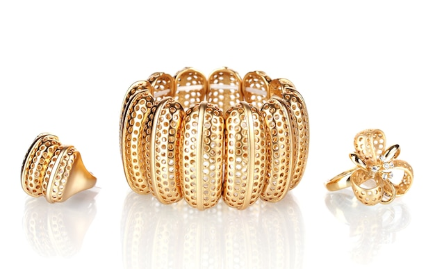 Schönes goldenes armband und ringe isoliert auf weiß