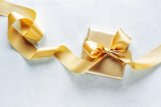 Schönes goldenes kastenweihnachtsgeschenk mit goldenem band auf weiß