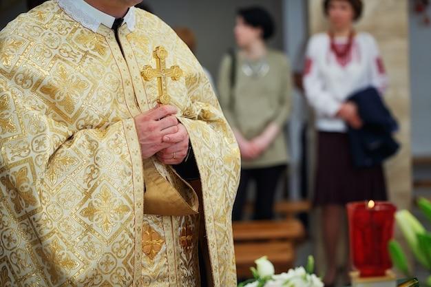 Schönes goldenes kreuz in den männlichen händen des priesters, der goldenes gewand auf zeremonie in christlicher kathedralenkirche, heiliges sakramentales ereignis trägt