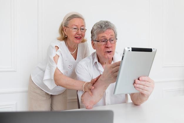 Schönes großelternpaar, das lernt, ein digitales gerät zu verwenden