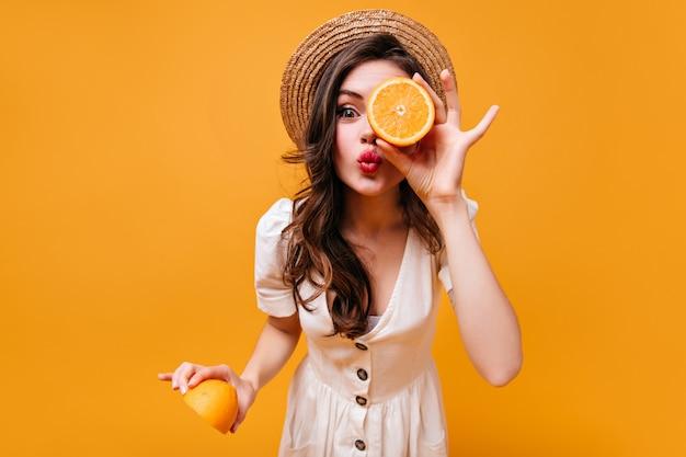 Schönes grünäugiges dunkelhaariges mädchen in hut und sommerkleid sendet kuss und posiert mit orangefarbenen hälften.