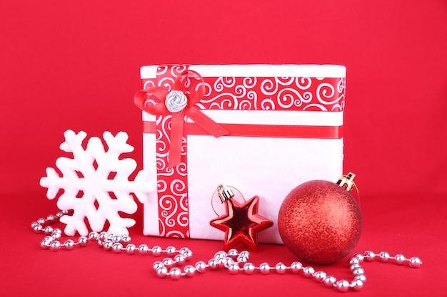 Schönes helles geschenk und weihnachtsdekoration auf roter oberfläche