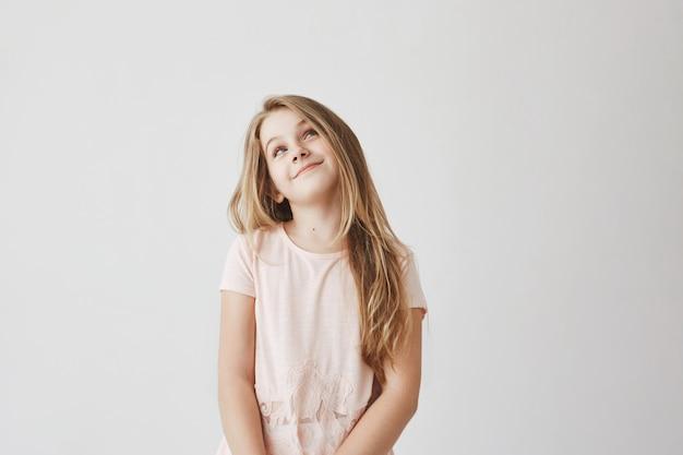 Schönes hellhaariges mädchen im rosa kleid, das oben mit foxy gesichtsausdruck schaut, über das lügen über markierungen in der schule denkend, um süßigkeiten von mutter zu erhalten.