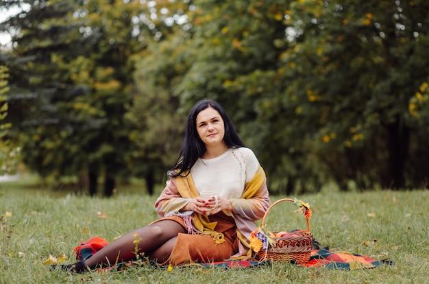 Schönes herbstmädchenporträt. junge frau, die über gelben blättern im herbst-park aufwirft. draussen
