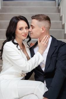 Schönes heterosexuelles paar, das auf der treppe sitzt und umarmt.