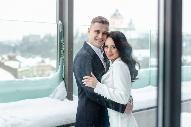 Schönes heterosexuelles paar, das draußen im winter umarmt