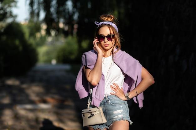 Schönes hipster-mädchen mit bandana und modischer sonnenbrille mit sweatshirt und weißem tanktop in stylischen jeans-shorts mit handtasche gehen auf der straße