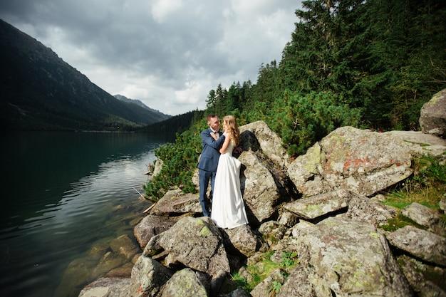 Schönes hochzeitsfoto auf bergsee. glückliches asiatisches paar in der liebe, braut im weißen kleid und bräutigam im anzug
