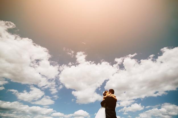 Schönes hochzeitspaar auf dem hintergrund des blauen himmels