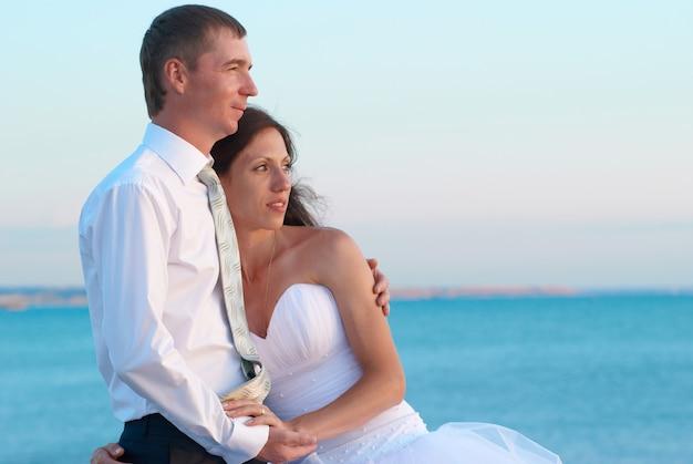 Schönes hochzeitspaar - braut und bräutigam, die am strand umarmen. gerade geheiratet