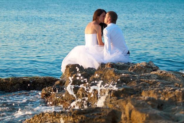Schönes hochzeitspaar - braut und bräutigam küssen sich am strand. gerade geheiratet