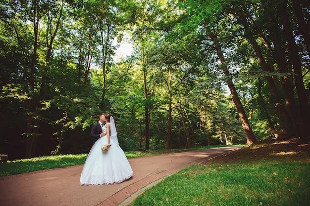 Schönes hochzeitspaar. die braut und der bräutigam am hochzeitstag, die draußen im frühling natur gehen. brautpaar newlywed glückliche frau und mann, die einen grünen park umarmen.
