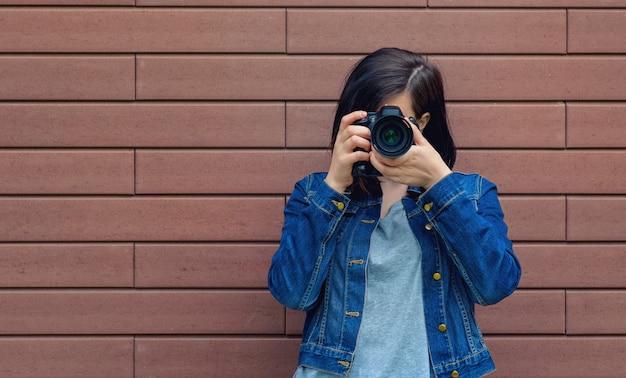 Schönes hübsches kaukasisches mädchen in einer blauen jeansjacke mit digitalkamera in den händen nahe einer braunen backsteinmauer.