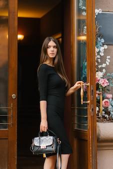 Schönes hübsches mädchen in einem schwarzen kleid, das eine schwarze tasche hält, öffnet sie die schönen holztüren