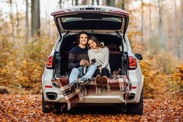 Schönes hübsches paar, das picknickzeit im wald genießt