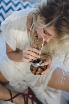 Schönes indisches hippiemädchen mit dem langen blonden haar auf trinkendem kameradentee des dachs.