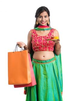 Schönes indisches junges mädchen, das mit einkaufstüten und pooja thali auf einem weißen raum hält und aufwirft