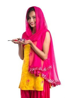 Schönes indisches junges mädchen, das pooja thali hält oder anbetung auf einem weißen raum durchführt