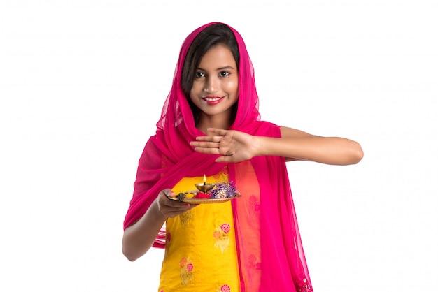 Schönes indisches junges mädchen, das pooja thali hält oder anbetung durchführt