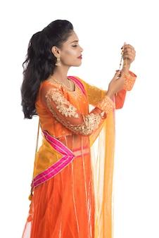 Schönes indisches mädchen, das rakhi anlässlich des raksha bandhan zeigt. schwester binden rakhi als symbol intensiver liebe zu ihrem bruder.