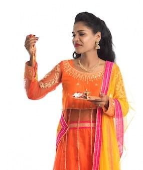 Schönes indisches mädchen, das rakhi mit pooja thali anlässlich von raksha bandhan zeigt. schwester binden rakhi als symbol intensiver liebe zu ihrem bruder.