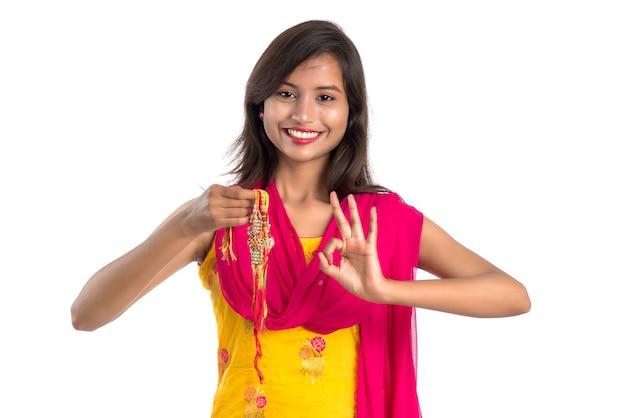 Schönes indisches mädchen, das rakhis anlässlich des raksha bandhan zeigt