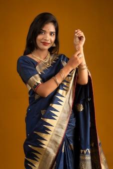 Schönes indisches mädchen, das rakhis anlässlich von raksha bandhan zeigt. schwester bindet rakhi als symbol intensiver liebe zu ihrem bruder.