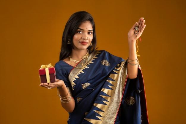 Schönes indisches mädchen, das rakhis und die geschenkbox anlässlich von raksha bandhan zeigt. schwester bindet rakhi als symbol intensiver liebe zu ihrem bruder.