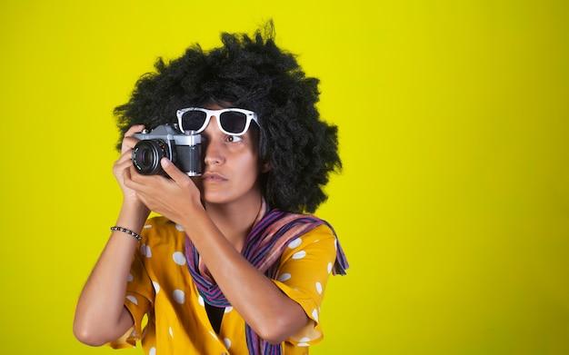Schönes indisches mädchen mit afro-lockiger frisur und weißen brillen, die bilder mit retro-kamera auf gelber wand sprechen