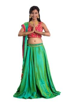 Schönes indisches mädchen mit willkommenem ausdruck, der namaste einlädt oder begrüßt