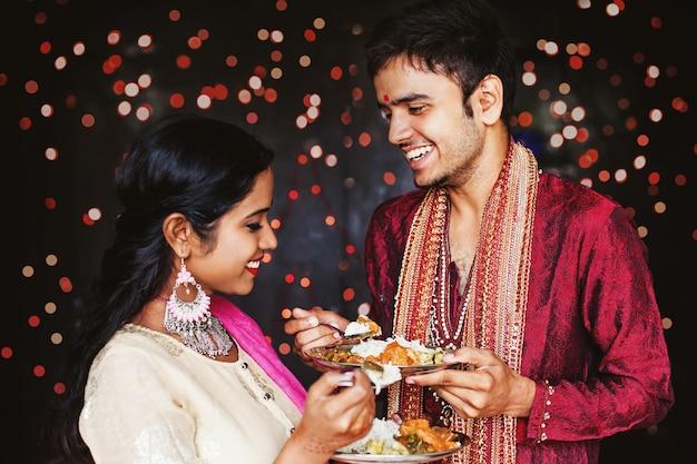 Schönes indisches paar, das essen über festlichem bokeh-hintergrund isst