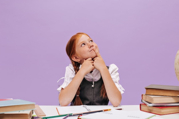 Schönes ingwer-kind mit sommersprossen in weißem, stilvollem hemd, das am schreibtisch mit büchern an isolierter lila wand denkt und sitzt