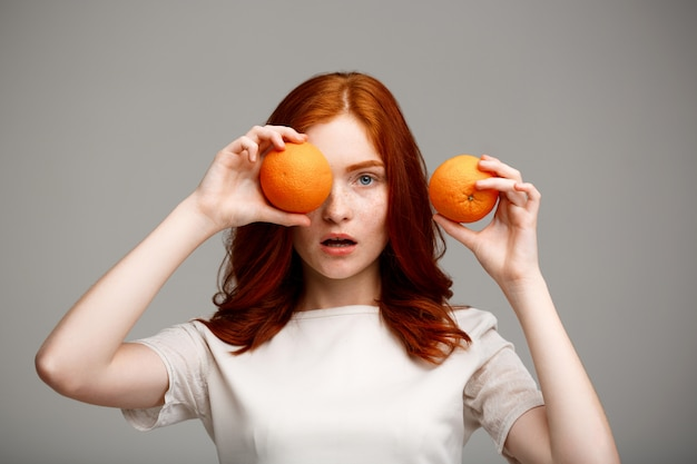 Schönes ingwermädchen, das orangen über graue wand hält.