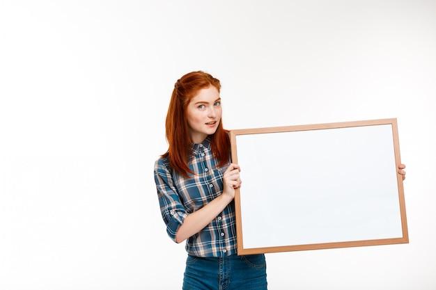 Schönes ingwermädchen mit whiteboard über weißer wand.