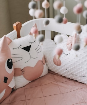 Schönes interieur des babyzimmers mit einer krippe mit kissen und rosa decke