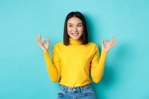 Schönes japanisches mädchen in gelbem pullover, zeigt ok-zeichen und lächelt, schaut nach links und logo und empfiehlt unternehmen, stehend auf blauem hintergrund