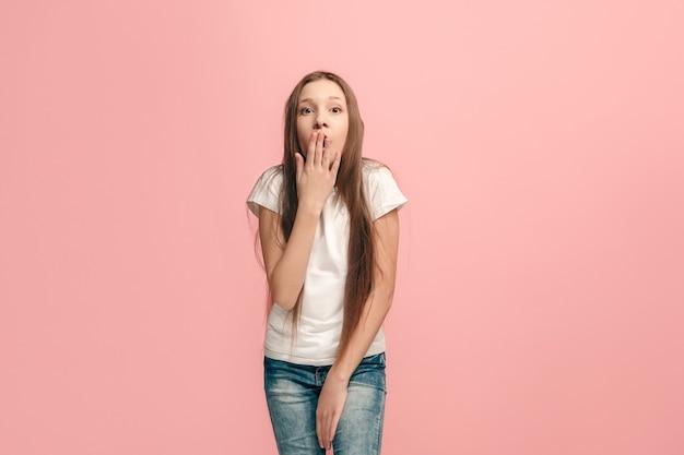Schönes jugendlich mädchen, das auf rosa lokalisiert überrascht sieht