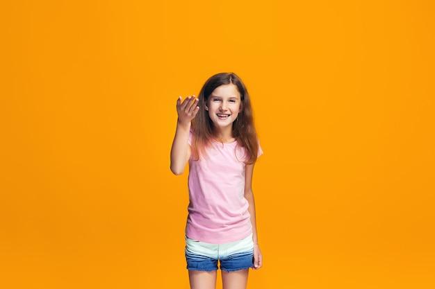 Schönes jugendlich mädchen, das überrascht auf orange sucht