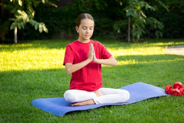 Schönes jugendlich mädchen, das yoga auf fitnessmatte im park praktiziert
