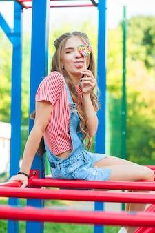 Schönes jugendlich mädchen in jeansoverall mit lutscher, der auf einer schaukel sitzt