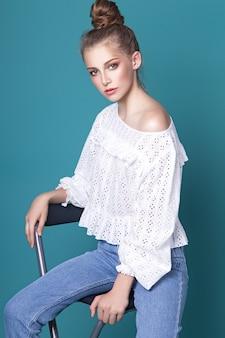 Schönes jugendlich mädchen mit gesammeltem haar, das im studio auf einem türkisfarbenen hintergrund aufwirft, gekleidet in eine weiße bluse und blaue jeans. modekonzept