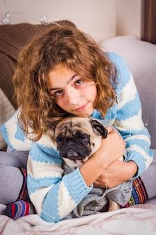 Schönes jugendlich mädchen umarmt einen pughund mit liebe. gelocktes mädchen in einer gestrickten strickjacke hält einen mops.