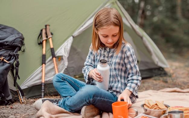 Schönes jugendliches mädchen, das im wald beim camping sitzt und tee aus der tasse trinkt