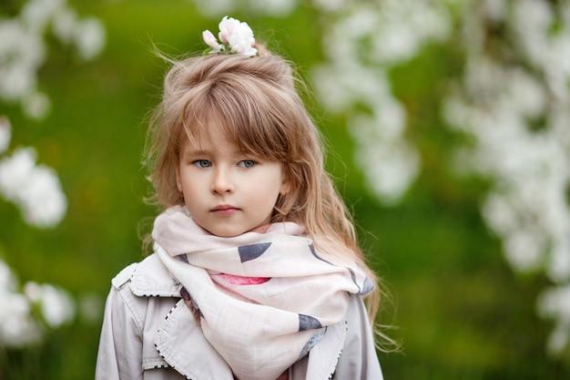 Schönes jugendliches mädchen mit langen blonden haaren genießen frühlingsapfelblüte. kleines mädchen in gartenbaumblumen. frühling.