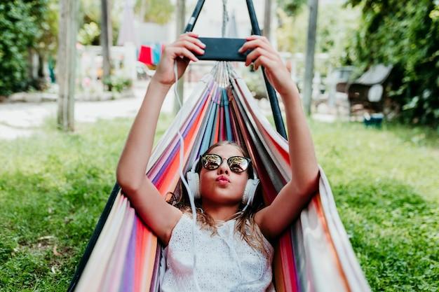 Schönes jugendlichmädchen, das auf bunter hängematte am garten liegt. musik auf handy und kopfhörer hören und lächeln. entspannen und spaß im freien